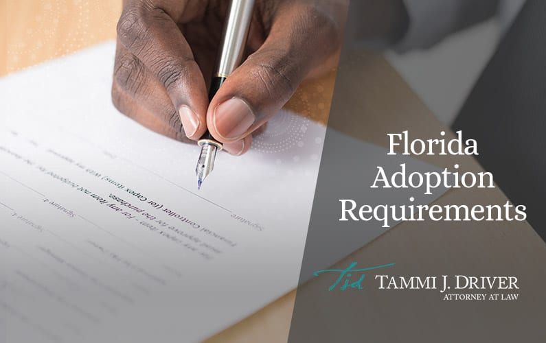Close up of the hand of a black man signing paperwork during the adoption process in Florida.