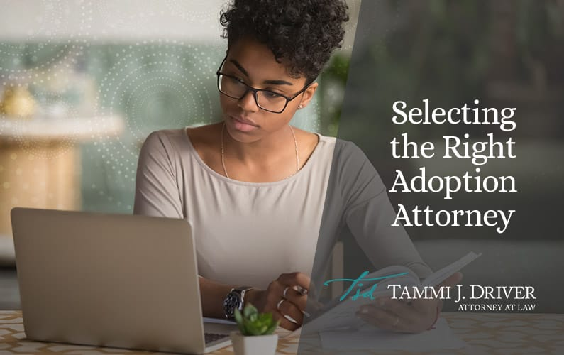 Woman searching on laptop for Florida adoption attorney and taking notes.